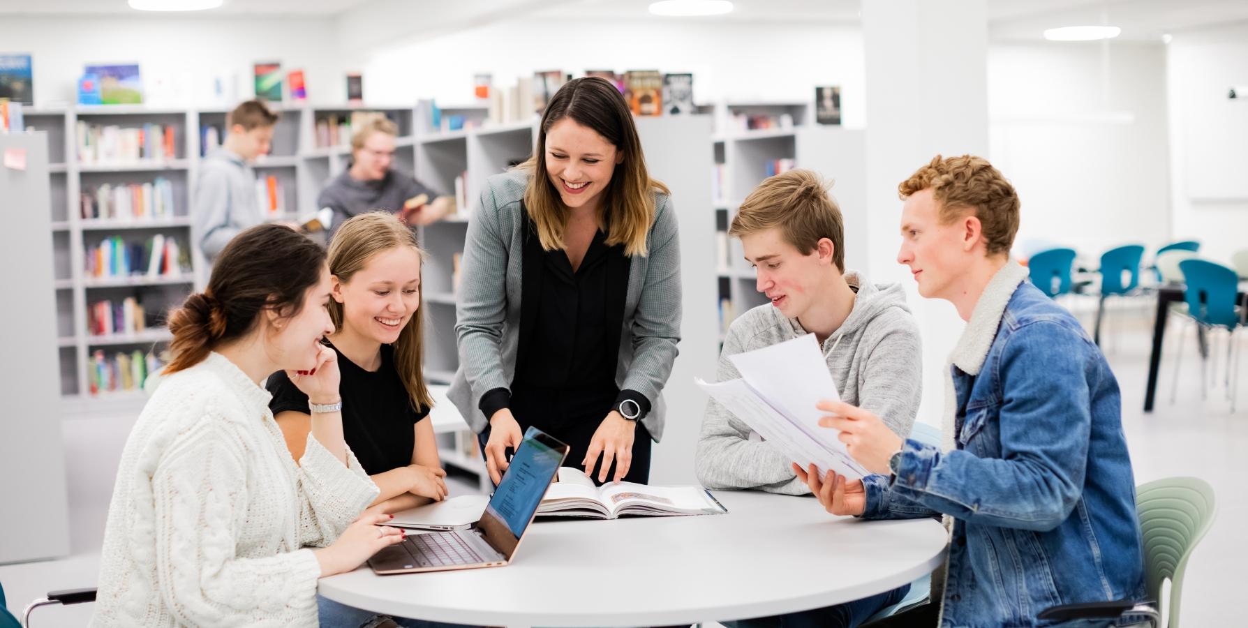 Foto av lærer som hjelp ungdommar som sitt rundt eit bord