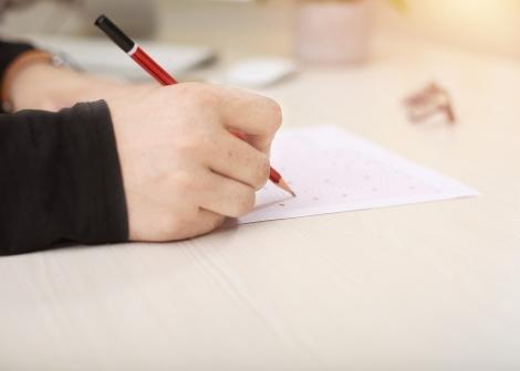 Foto av ei hand som held ein blyant og skriv på eit ark