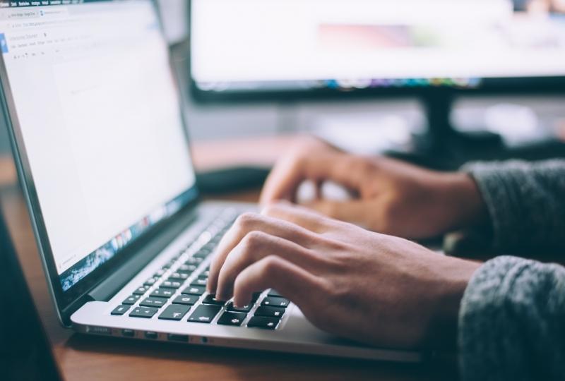 Foto av hender som skriver på tastaturet til en bærbar datamaskin