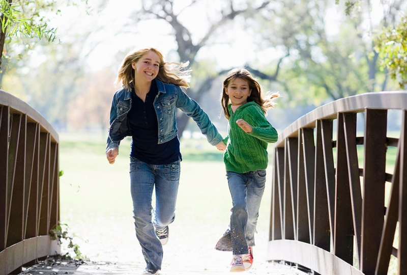 Foto av to glade unge jenter som løper hånd i hånd over en bro