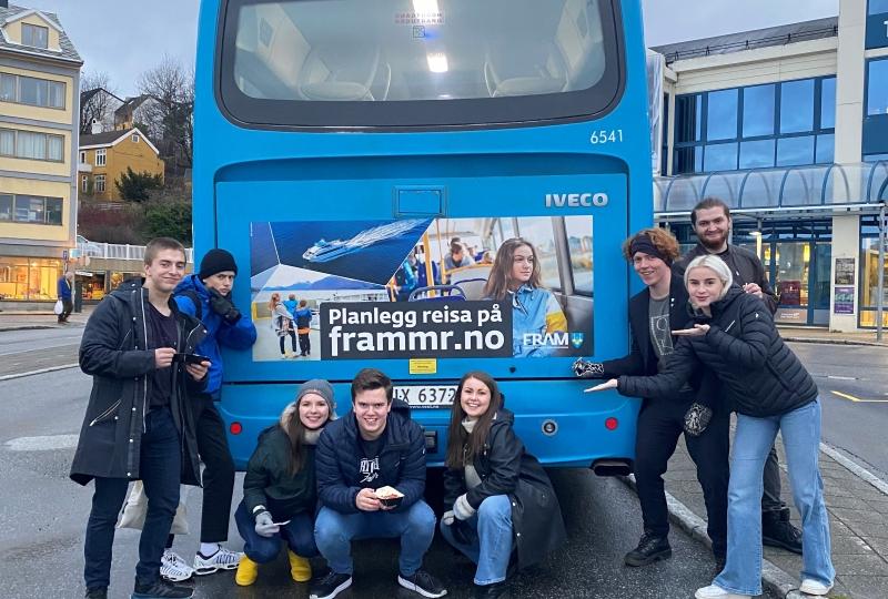 Foto av ungdommar som står ved bakenden til ein buss