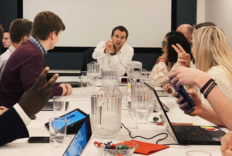 Foto av personar som sitt rundt eit møtebord