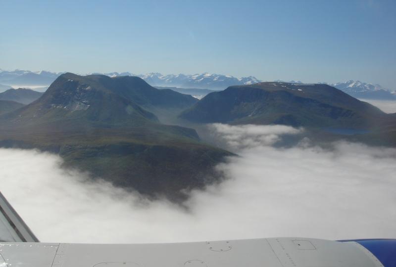 Foto av fjell med blå himmel, sett frå eit flyvindu