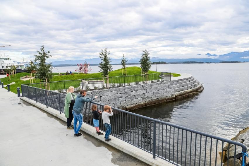 Ei kvinne, ein mann og to barn ser ut mot fjella frå brua ved politistasjonen i Molde
