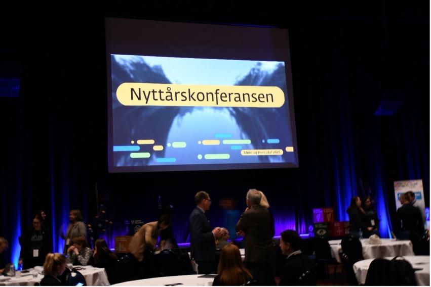 Foto av mennesker som står foran ei scene med teksten Nyttårskonferansen