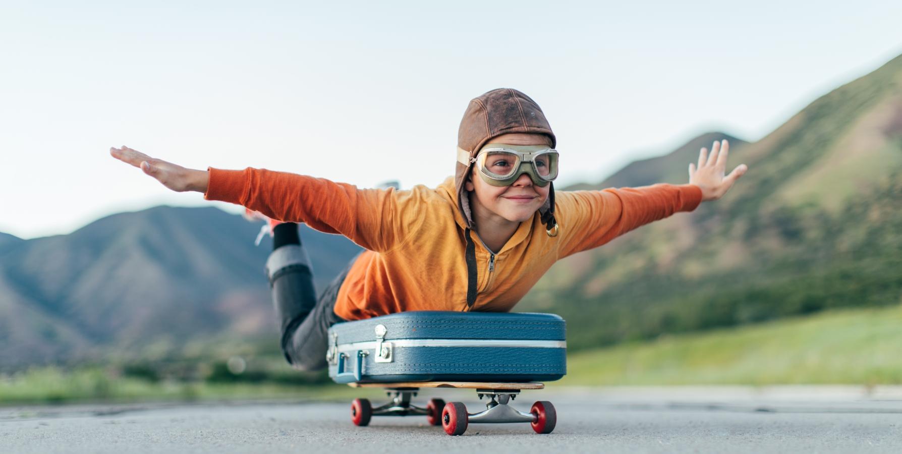 Bilde av gutt som ligg på ein koffert på eit rullebrett