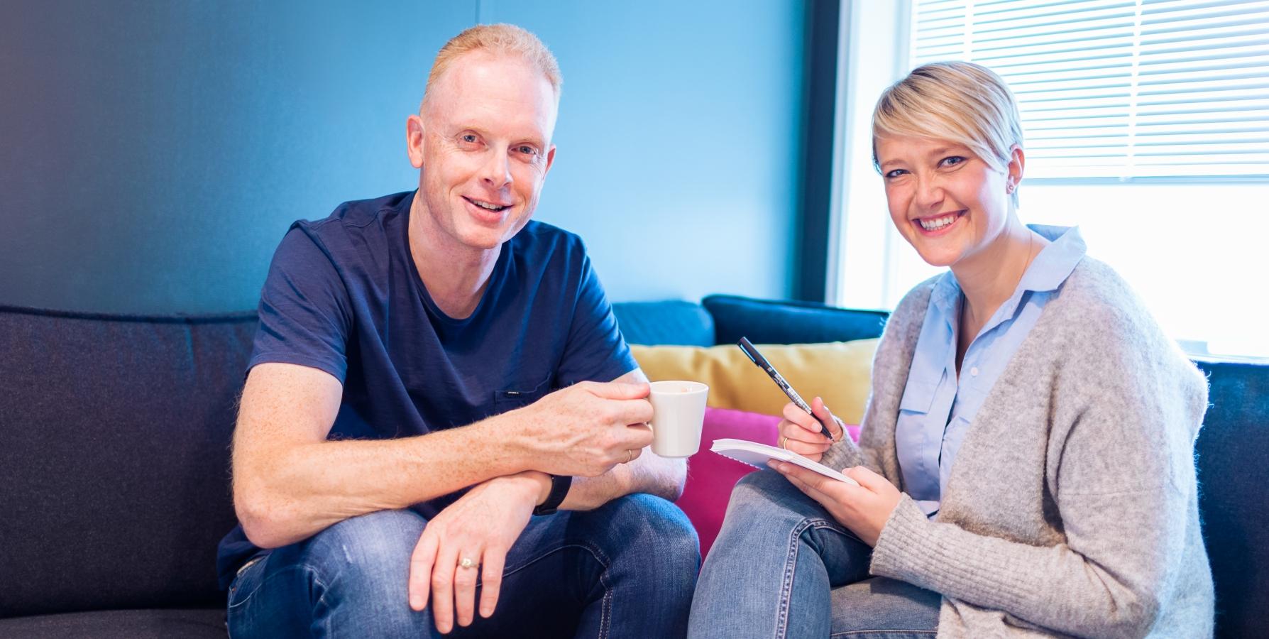 Foto av mann og dame sittende i sofa