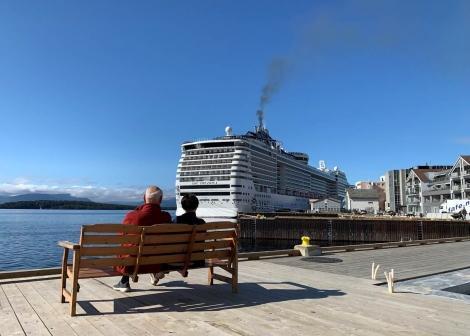 To personar som sitt på ein benk og ser på ein Cruisebåt som ligg til kai