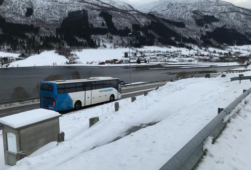 Bilde av ein buss som køyrer påvinterveg