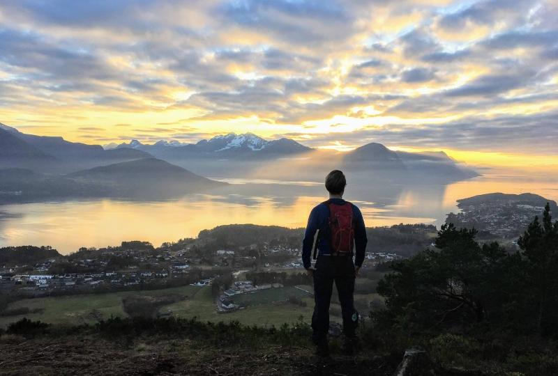 Foto av ein mann som står og ser på utsikt over fjord og fjell