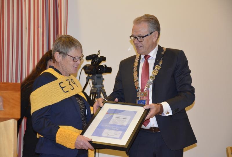 Foto av ei kvinne og ein mann som held ein diplom