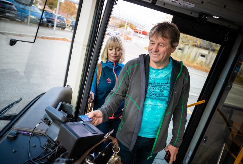 Nærbilde av to passasjer går på buss framme og skal betale.