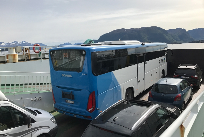 Foto av ein buss som står på ei ferje med bilar rundt