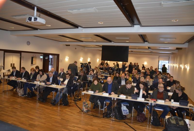 Foto av folk som sitt ved møtebord i ein stor sal